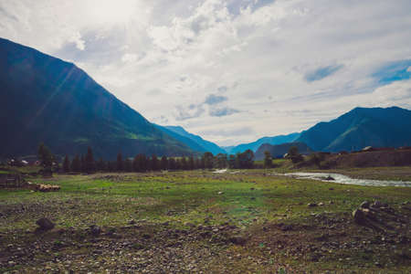 Village in valley. Livestock in highlands on background of giant mountains in sunlight. Sheeps graze near mountain river in sunny rays. Amazing atmospheric landscape of majestic nature. Standard-Bild - 124054268