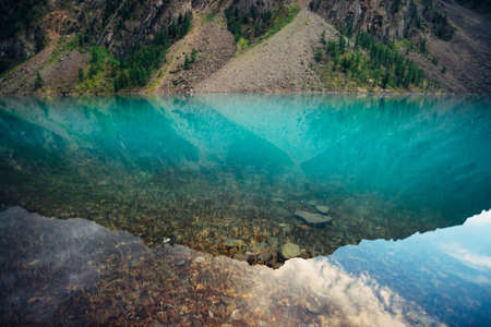 Plants and stones on bottom of mountain lake with clean water close-up. Giant mountain range reflected on smooth water surface. Background with underwater vegetation. Reflection of huge mountain ridge Standard-Bild - 124054384