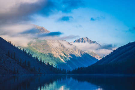 Amazing blue silhouettes of mountains under blue cloudy sky. Beautiful ripples on water of mountain lake. Low clouds before mountain ridge. Wonderful highland landscape. Picturesque mountainscape. Standard-Bild - 124054275