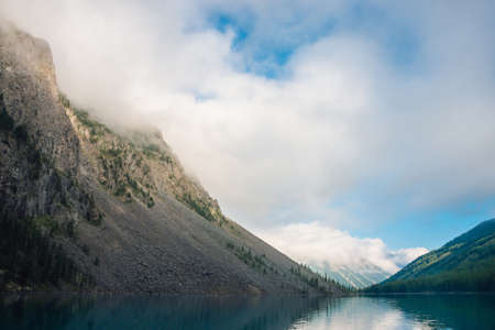 Giant cloud above mountains with trees in sunlight. Amazing mountain lake. Mountain range under blue cloudy dawn sky. Wonderful rocks. Morning landscape of highland nature. Low clouds in sunny light.