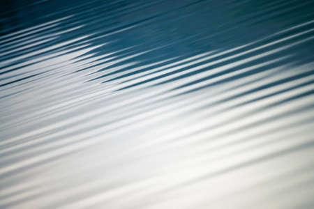 Amazing textured background of calm blue clean water surface. Sunshine in mountain lake close-up. Beautiful ripples on shiny water in sunny day. Wonderful relax texture. Standard-Bild - 124054366