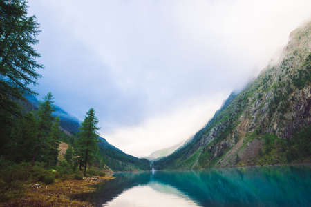 Amazing mountain lake in overcast weather. Mountains, cloudy sky and morning sunlight reflected in clear water. Coniferous trees near water. Stony bottom in transparent lake. Atmospheric landscape. Standard-Bild - 124054369