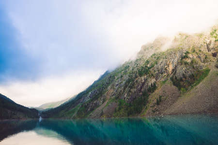 Giant rocks with trees in morning fog reflected in water of mountain lake. Early sun is shining through mist. Overcast weather. Atmospheric mountain landscape of majestic nature. Standard-Bild - 124054378