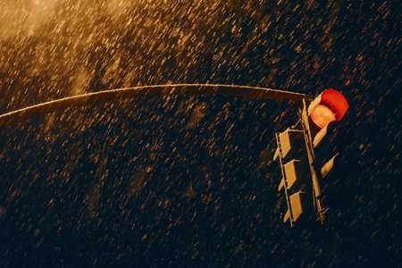 Red traffic signal in dark time close up. Traffic light at strong snowfall. Huge snowflakes above road. Stop signal in night. Atmospheric background with copy space. Traffic Laws. No traffic. Standard-Bild - 124054379