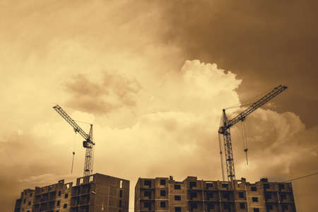 Cranes above unfinished multistorey panel building on background of cloudy sky with copy space in sepia tones. Process of construction of apartment building in overcast weather close up in monochrome.