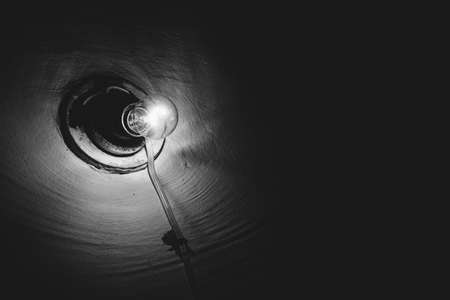 Incandescent lamp burns inside dark room close-up. Illumination. Old light bulb on rough wall. Lamp illuminate basement in grayscale. Light in darkness. Minimalist monochrome background. Copy space. Standard-Bild - 124054515