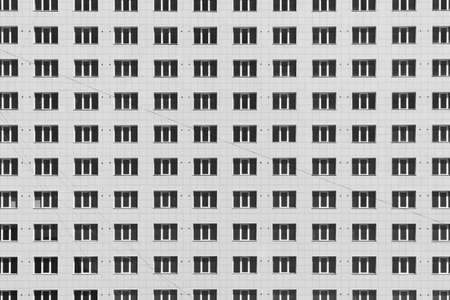 Geometric background with lots of window rows. Modern building texture. Office construction. Apartment building close-up. Many windows on huge wall. European classic high-rise building with copy space Standard-Bild - 124054513