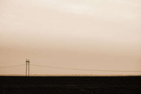 Power lines on background of sky close-up. Silhouette of electric pole with copy space in sepia tones. Wires of high voltage above ground. Electricity industry in monochrome.