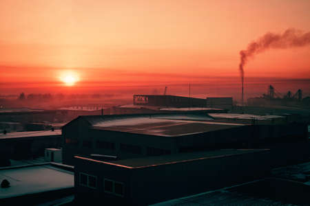 Storage of goods in warehouses in winter. Smoke from pipe pollutes environment in dawn. View from above of industrial area in sunrise in pink tones. Industrial buildings zone close up with copy space. Standard-Bild - 124054526