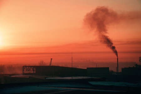 Smoke from pipe pollutes environment in dawn. Storage of goods in warehouses in winter. View from above of industrial area in sunrise in pink tones. Industrial buildings zone close up with copy space. Standard-Bild - 124054719