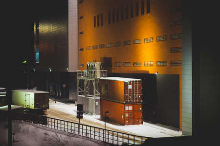 Truck with trailer parked near container in industrial area in winter night with copy space. Orange wall of warehouse building close up. Cargo in containers on background big wall. Transport company. Standard-Bild - 124054733