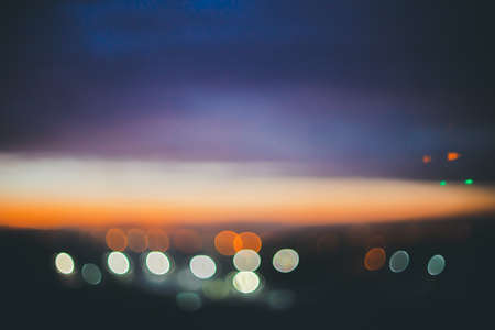 Wonderful atmospheric calm dawn above city. Amazing picturesque romantic sunset. City lights in bokeh. Cozy abstract blurred background of scenic sunrise. Tranquil scenery. Vintage landscape. Standard-Bild - 124054551