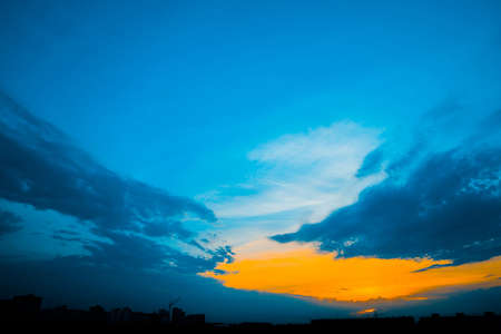 Atmospheric blue cloudy sky behind silhouettes of city buildings. Cobalt and orange background of sunrise with dense clouds and bright yellow sunny light for copy space. Cyan heaven above clouds. Standard-Bild - 124054718