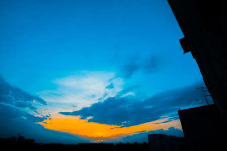 Atmospheric blue cloudy sky behind silhouettes of city buildings. Cobalt and orange background of sunrise with dense clouds and bright yellow sunny light for copy space. Cyan heaven above clouds. Standard-Bild - 124054717