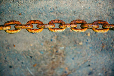 Old oxidized rusty chain hanging over asphalt close up with copy space. Conceptual vivid background with thick links of strong chain. Artwork. Standard-Bild - 124054769