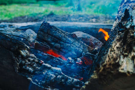 Smoldered logs burned in vivid fire close up. Atmospheric background with orange flame of campfire. Unimaginable detailed image of bonfire from inside with copy space. Smoke and glowing embers in air. Standard-Bild - 125153900