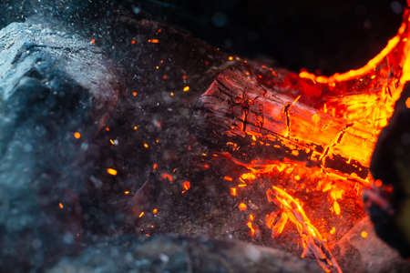 Smoldered logs burned in vivid fire close up. Atmospheric background with flame of campfire. Unimaginable detailed image of bonfire from inside with copy space. Whirlwind of smoke and glowing embers. Standard-Bild - 125153901