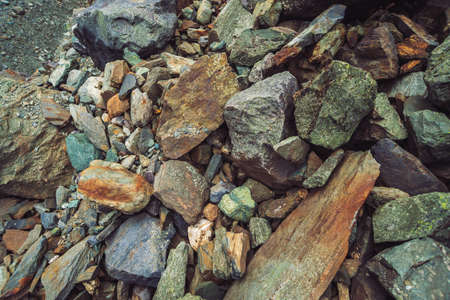 Multicolored boulder stream. Loose rock close up. Randomly scattered stones in nature. Amazing detailed background of highlands boulders with mosses and lichens. Natural texture of mountain terrain. Foto de archivo