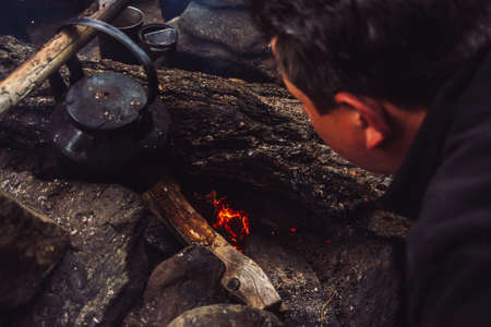 How to make fire. Tourist kindles bonfire. Traveler is lighting fire in camp. Man makes campfire in twilight. Active outdoor recreation. Camping in dusk. Active rest into wild. Man blowing on coals. 写真素材 - 125153842