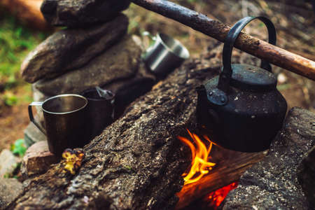 Boiling of tea in kettle on bonfire with large firewood. Tea drinking in open air. Active outdoor recreation. Camping in dusk. Romantic warm atmosphere in twilight on nature. Active rest. Metal mug. 写真素材 - 125153844