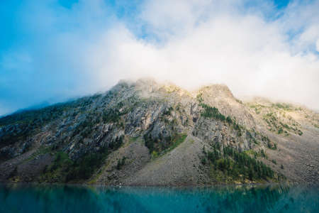 Giant cloud above rocky ridge with trees in sunlight. Amazing mountain lake. Mountain range under blue cloudy dawn sky. Wonderful rocks. Morning landscape of highland nature. Low clouds in sunny light
