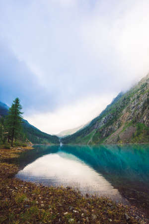 Amazing mountain lake in overcast weather. Mountains, cloudy sky and morning sunlight reflected in clear water. Coniferous trees near water. Stony bottom in transparent lake. Atmospheric landscape. Standard-Bild - 125153859
