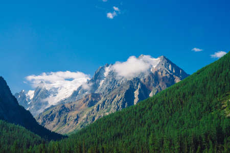 Giant rock in sunny day. Rocky ridge with snow behind hills with conifer forest cover. Clouds on top of huge snowy mountain range under blue sky. Atmospheric highland landscape of majestic nature. 写真素材 - 125153862