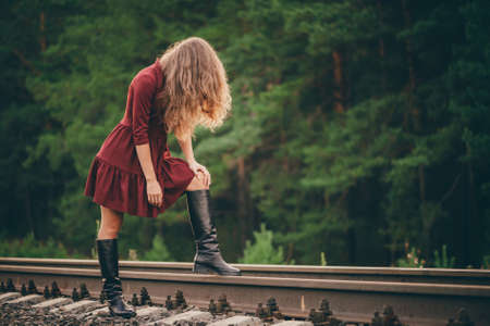 Beautiful sad girl is hiding face by hair. Moody lady in burgundy dress in forest on railway. Depressed lonely girl on railroad at dawn. Sun in curly natural hair in autumn. Bad mood. Offended girl. 写真素材 - 125153896