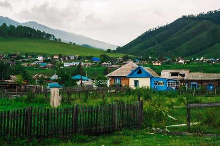 Modern village in mountains in overcast weather. Countryside in valley. Plot of land behind fence. Amazing mountain landscape with houses under cloudy sky.