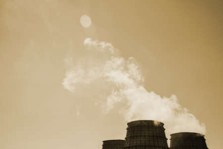 Three big tower of CHPP close-up. Steam from wide pipe of CHP on sky. Industrial background of TPP in sepia tones with copy space. Huge pipes of thermal power plant produce steam for electric power. Standard-Bild - 125984991