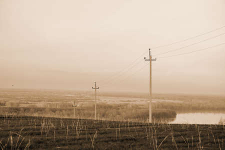 Atmospheric landscape with power lines in field on background of river under sepia sky. Electric pillars with copy space. Wires of high voltage above ground. Electricity industry in monochrome. 写真素材 - 125984993