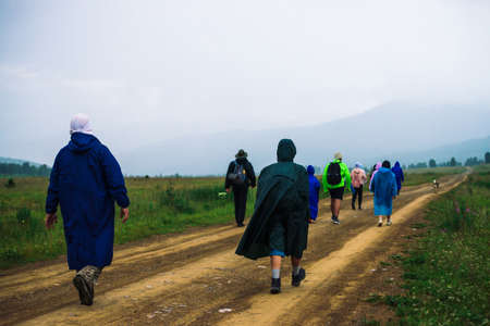 People go forward in mountain despite bad weather. Travelers goes upwards along road after dog. Way on foot in highlands in rainy overcast day. Summit despite everything. Walking in mountains. Standard-Bild - 125984998