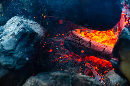 Smoldered logs burned in vivid fire close up. Atmospheric background with flame of campfire. Unimaginable detailed image of bonfire from inside with copy space. Whirlwind of smoke and glowing embers. Standard-Bild - 125985002