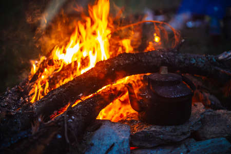 Boiling of tea in kettle on bonfire with large firewood. Tea drinking in open air. Active outdoor recreation. Camping in dusk. Romantic warm atmosphere in twilight on nature. Active rest. 写真素材 - 126155755