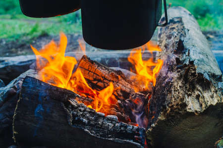 Cauldron and kettle above bonfire. Cooking of food on nature. Dinner outdoors. Firewood and branches in fire. Active rest. Camping in forest.
