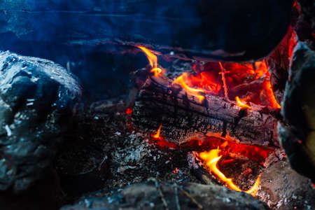 Smoldered logs burned in vivid fire. Atmospheric background with orange flame of campfire. Unimaginable detailed image of bonfire from inside with copy space. Smoke and ashes close up. Standard-Bild - 126155759