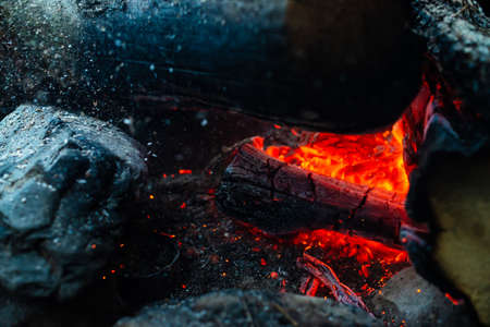 Smoldered logs burned in vivid fire. Atmospheric background with orange flame of campfire. Unimaginable detailed image of bonfire from inside with copy space. Whirlwind of smoke and ash close up. 写真素材 - 126155760
