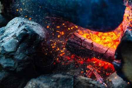 Smoldered logs burned in vivid fire close up. Atmospheric background with flame of campfire. Unimaginable detailed image of bonfire from inside with copy space. Whirlwind of smoke and glowing embers. Standard-Bild - 126155761