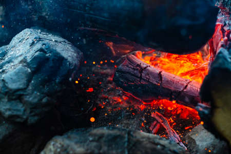 Smoldered logs burned in vivid fire close up. Atmospheric background with orange flame of campfire. Unimaginable detailed image of bonfire from inside with copy space. Smoke and glowing embers in air. 写真素材 - 126155762