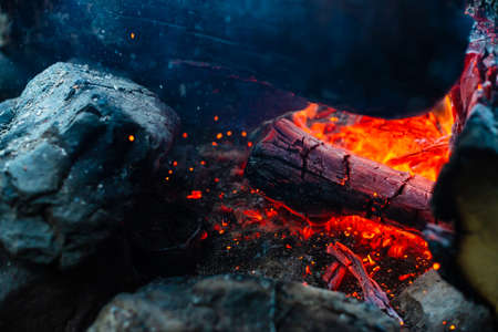 Smoldered logs burned in vivid fire close up. Atmospheric background with orange flame of campfire. Unimaginable detailed image of bonfire from inside with copy space. Smoke and glowing embers in air. 写真素材