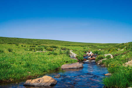 Traveler with camera on stone in mountain creek. Adventure of tourist. Hiking in mountains. Rich vegetation of highlands. Stream of clear water in brook. Vivid sunny landscape of majestic nature. 写真素材 - 126453847