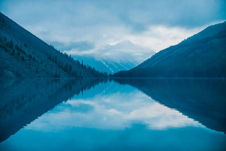 Amazing silhouettes of mountains and low clouds reflected on mountain lake. Beautiful ripples on water mirror. Cloudy sky in highlands.