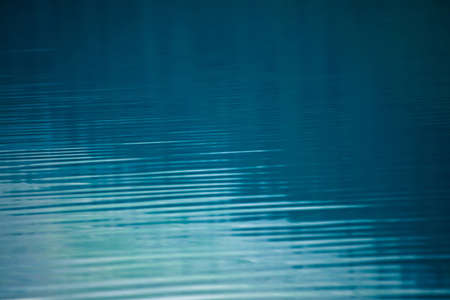 Amazing textured background of calm blue clean water surface. Sunshine in mountain lake close-up. Beautiful ripples on shiny water in sunny day. Wonderful relax texture. Stok Fotoğraf