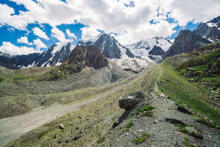 Hiking trail leads to huge snowy mountains in sunny day. Wonderful glacier in sunlight. Water streams on mountain. Rich vegetation of highlands. Atmospheric sunny minimalists landscape of nature.