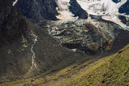 Foothills of giant glacier. Amazing rocky relief with snow and ice. Wonderful huge mountain rocky natural wall with small waterfalls. Water from glacier. Fantastic artwork of majestic highland nature.