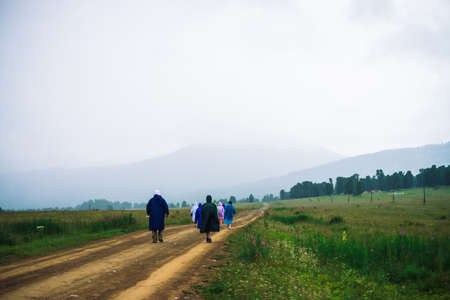 People go forward in mountain despite bad weather. Travelers goes upwards along road. Way on foot in highlands in rainy overcast day. Summit despite everything. Walking in mountains. Stock Photo