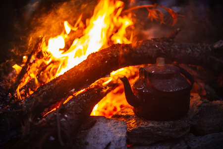 Boiling of tea in kettle on bonfire with large firewood. Tea drinking in open air. Active outdoor recreation. Camping in dusk. Romantic warm atmosphere in twilight on nature. Active rest.