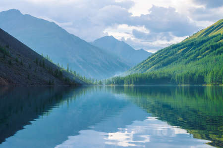 Ghostly mountain lake in highlands at early morning. Beautiful misty mountains reflected in calm clear water surface. Smoke of campfires. Amazing atmospheric foggy landscape of majestic nature.