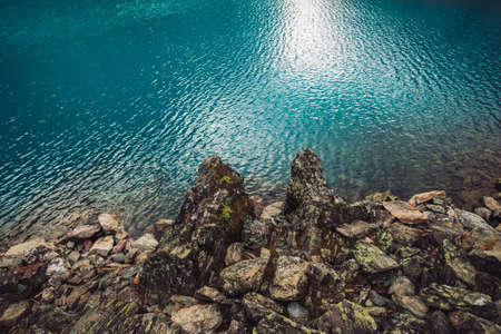 Rocky shore. Water edge. Shiny surface of azure mountain lake. Stony bottom in transparent water. Minimalist blue background. Reflection of mountains on clear water. Vegetation on stones. Copy space.