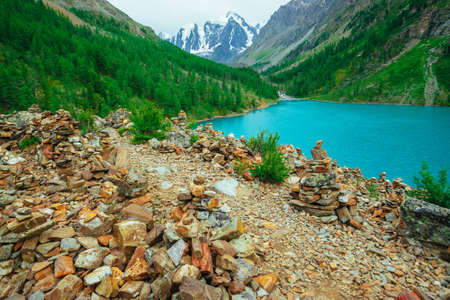 Pyramids of balancing stones on stony hill on background of glacier and mountain lake. Rich vegetation of highlands. Conifer forest on mountainside. Wonderful mountains. Amazing vivid green landscape.